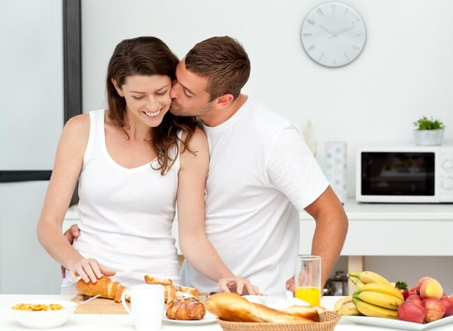 man-kisses-woman-preparing-breakfast[1]